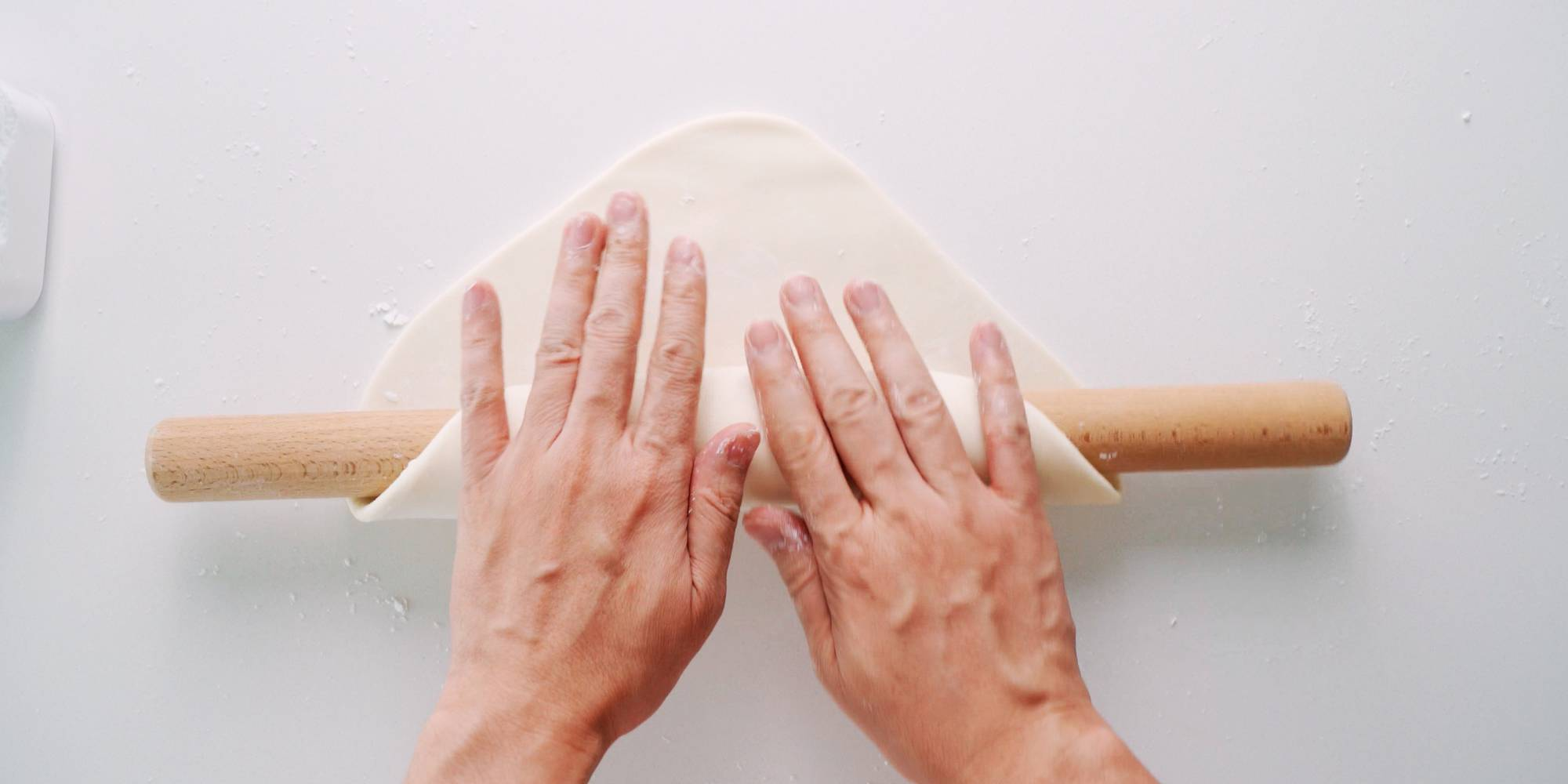 Rolling udon dough onto rolling pin.