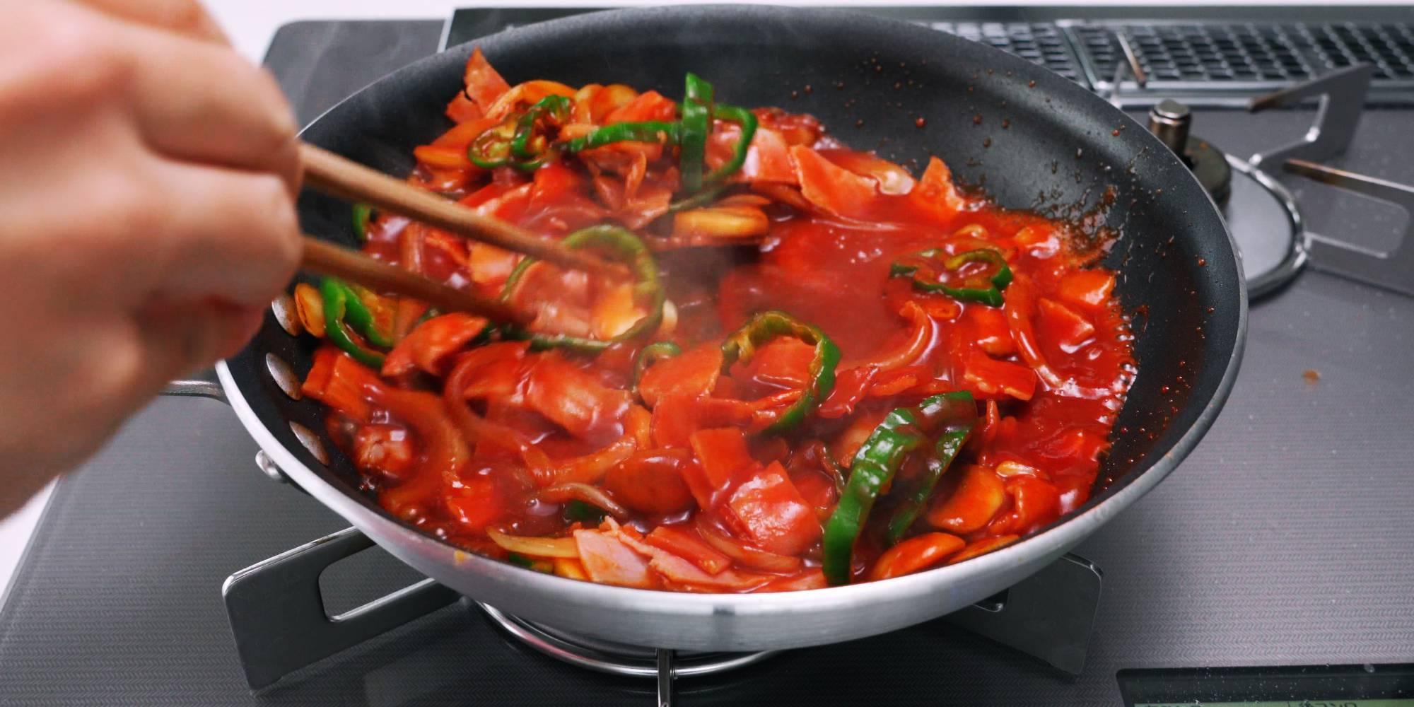 Spaghetti Napolitan sauce simmering in a frying pan.