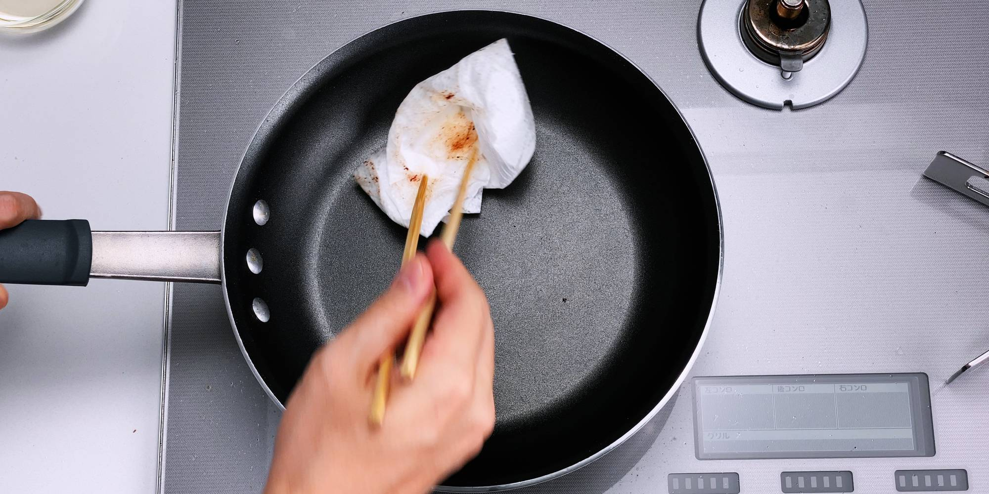 Wiping out oil and debris from frying pan with paper towels.