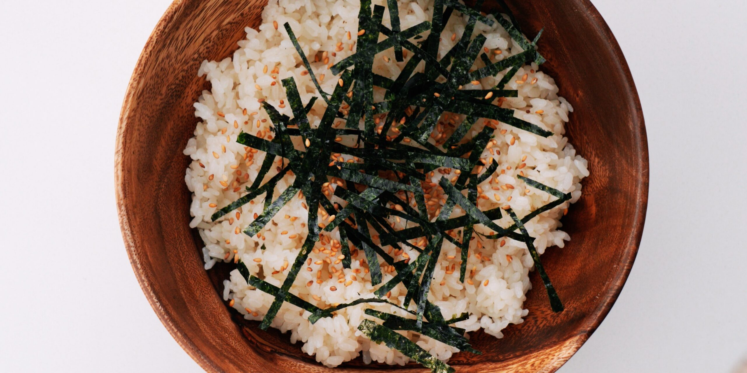 Sushi rice, nori and sesame seeds in a wooden bowl.