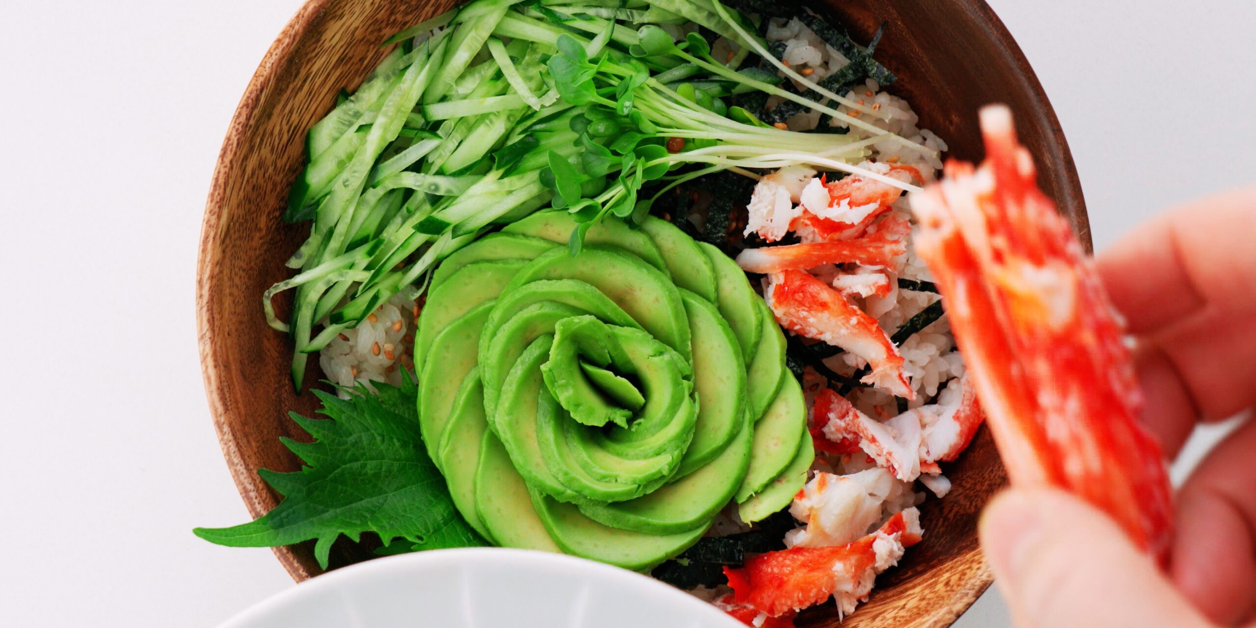 Avocado and crab on top of sushi rice.