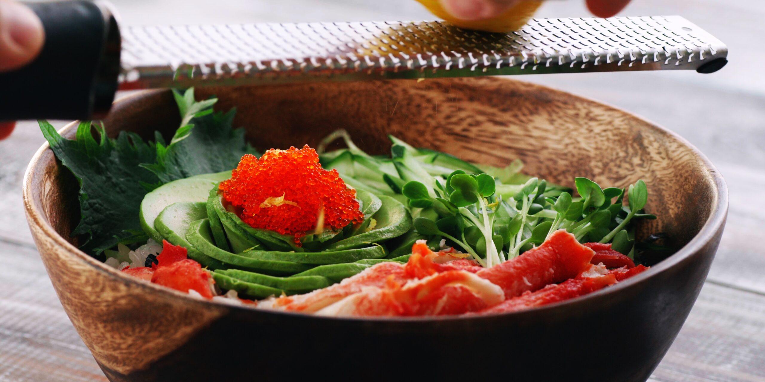 Grating yuzu zest onto a California Roll sushi bowl.