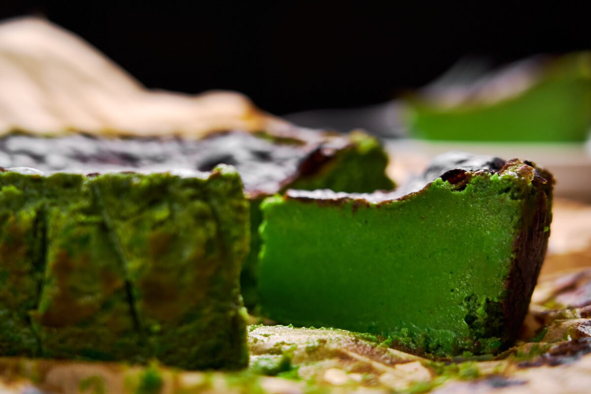 A slice of Matcha Basque Cheesecake with a custardy smooth green tea center and caramelized top.