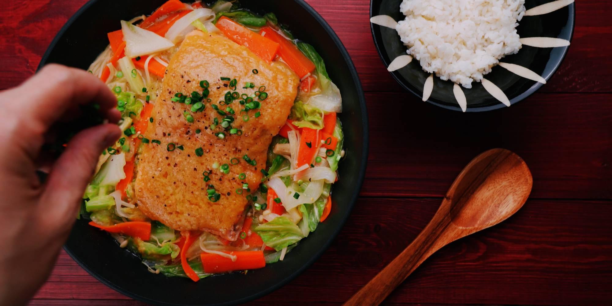 Garnishing Chan Chan Yaki with scallions and black pepper.