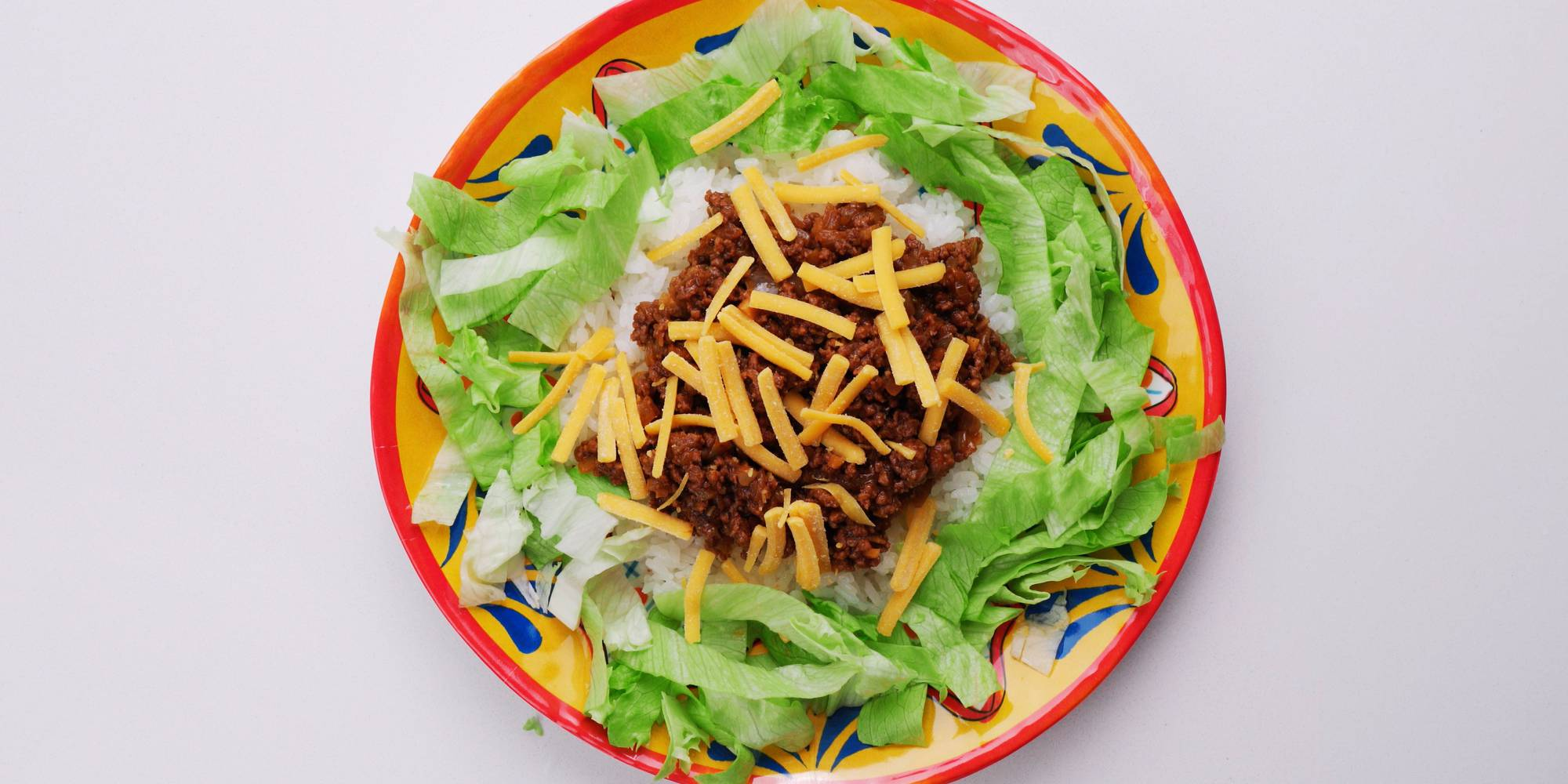 Rice and lettuce with taco meat and cheese.