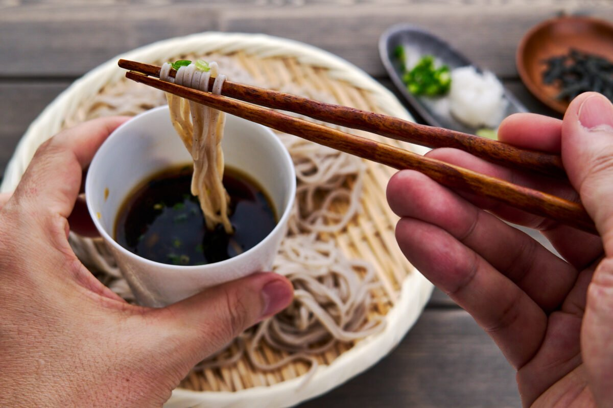 Cold soba noodles get dipped in an umami-packed dashi stock loaded with condiments.