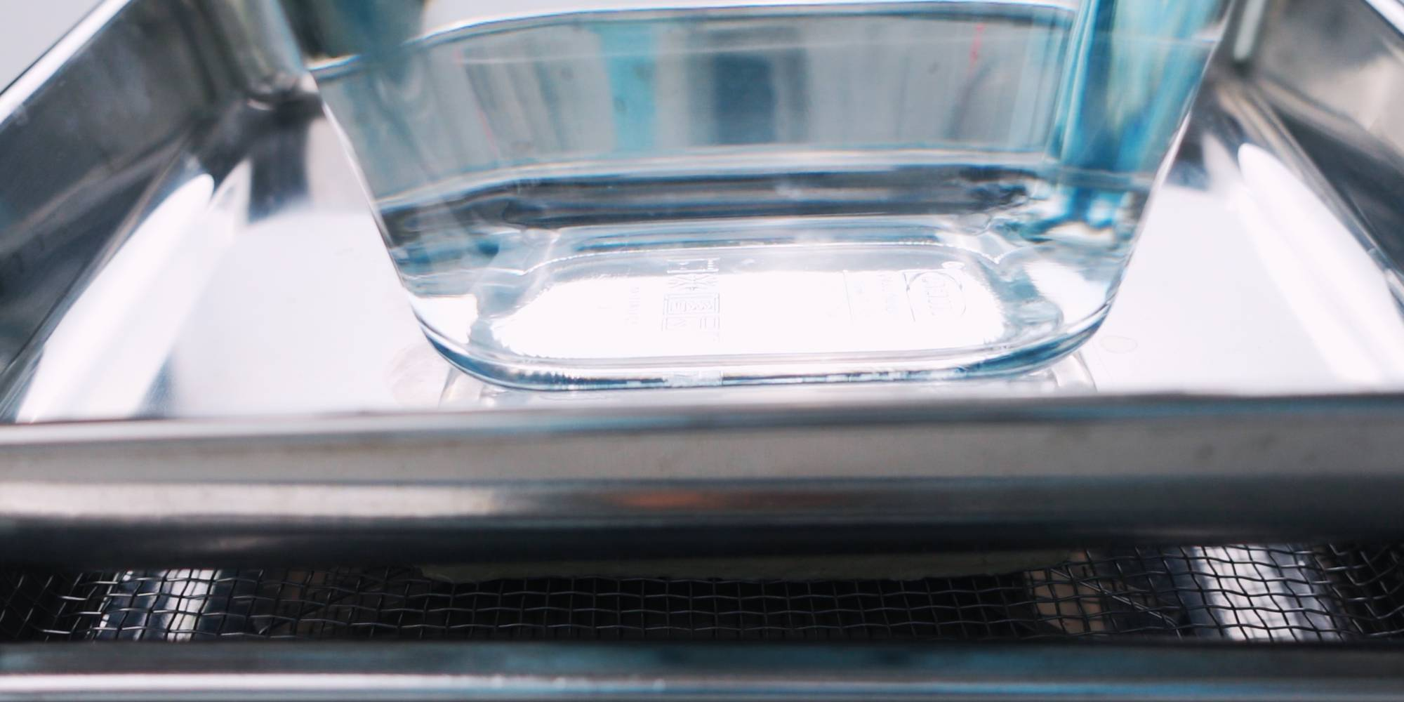 Pressing tofu under a weight to remove excess moisture.