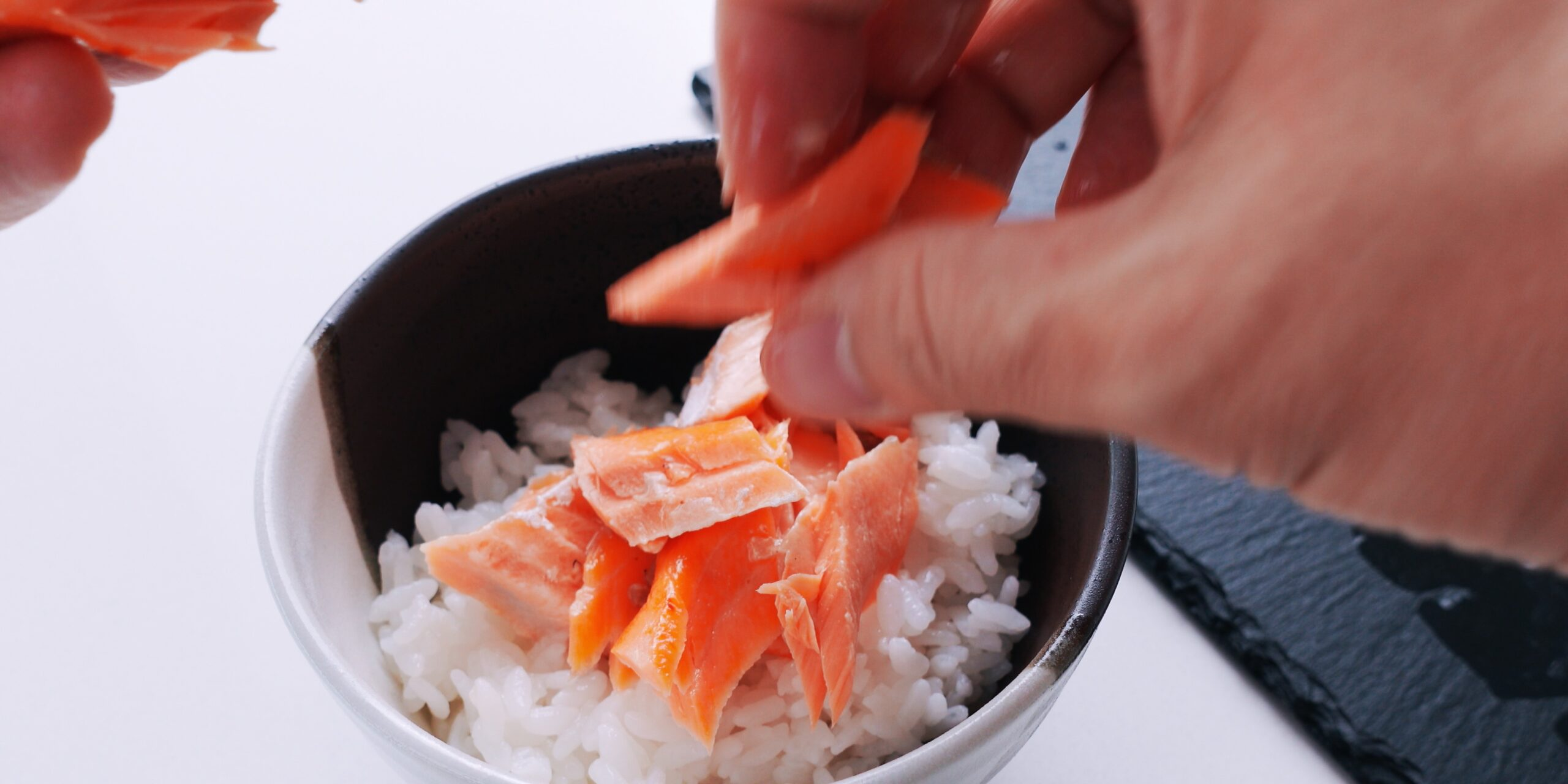 Flaking salmon on top of a bowl of rice.