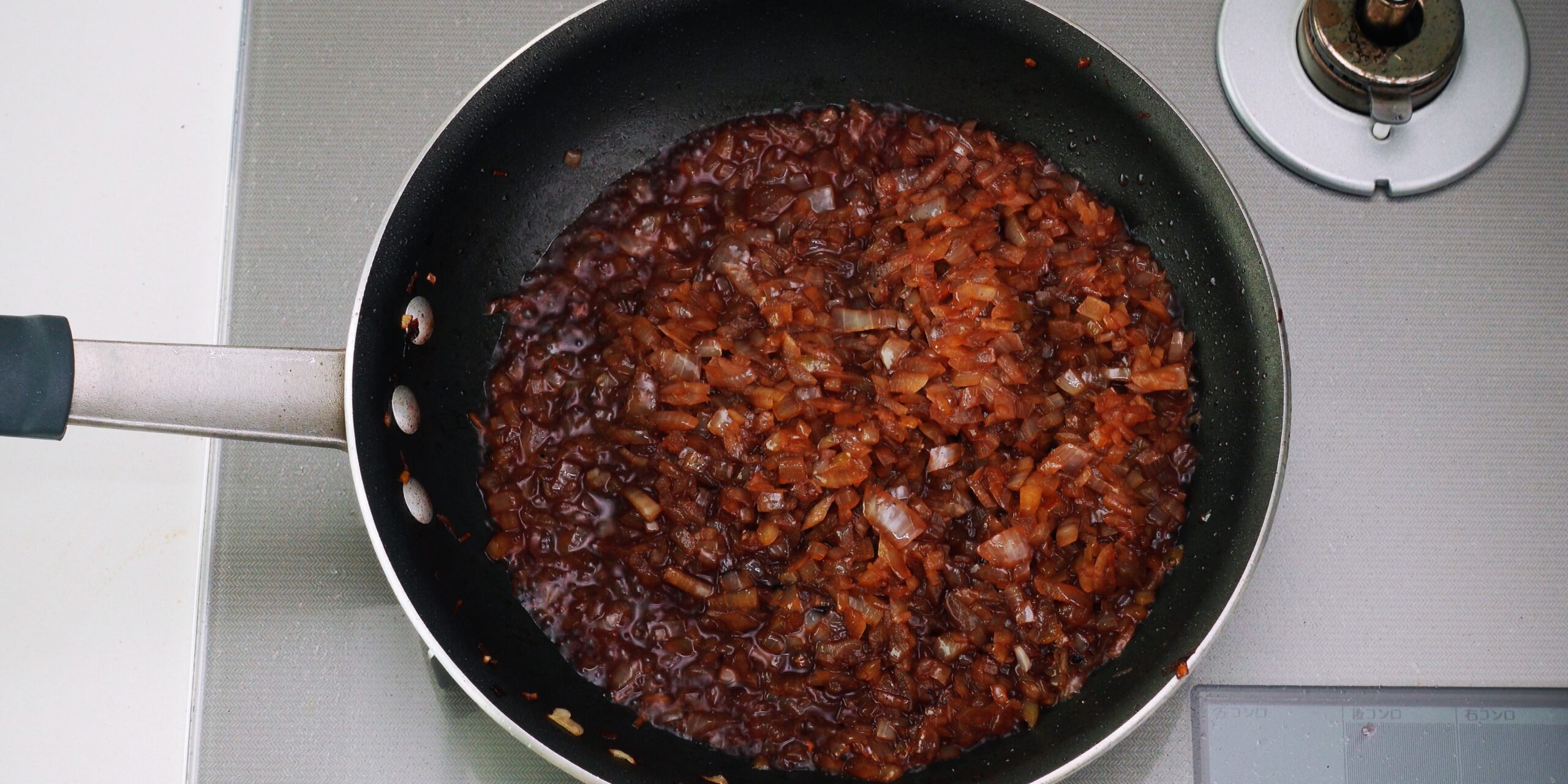 Pan of sauteed onions being deglazed with red wine.